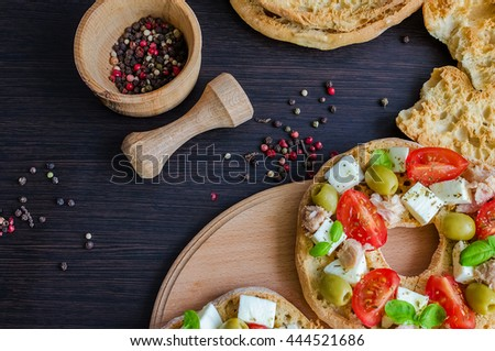 Italian appetizer Friselle. Italian dried bread Friselle with tomatoes cherry, cheese mozzarella, olives, tuna, basil and pepper in wooden pounder. Italian food. Healthy vegetarian food. Top view. - stock photo