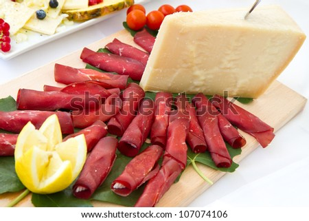 Italian appetizer with bresaola and parmesan cheese - stock photo