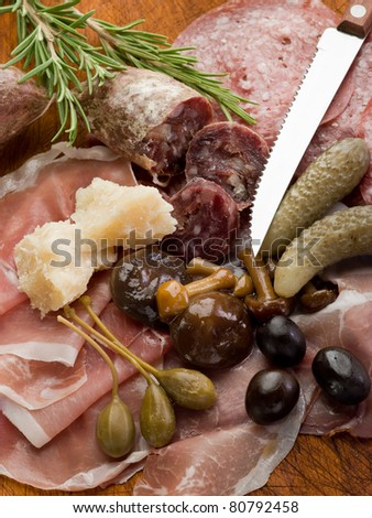 italian appetizer with salami, grana,speck,mushroom,cucumber and olives - stock photo