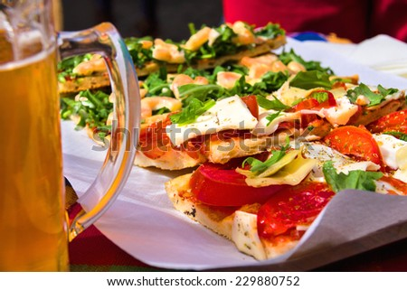 Italian appetizers and mug of beer in a restaurant - stock photo