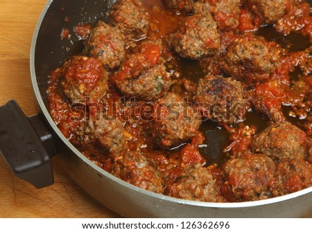 Italian beef meatballs being cooked in a spicy tomato sauce.