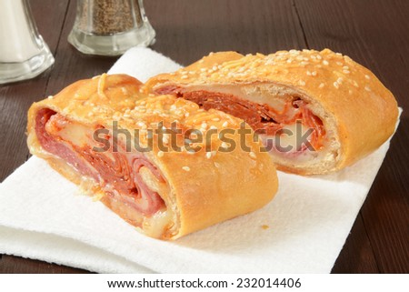 Italian bread roll sandwich with pastrami, cheeses and salami - stock photo
