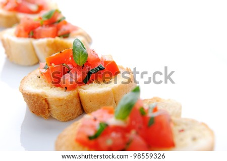 Italian bruschetta; sliced baguette topped with a mixture of chopped tomato, garlic and basil - stock photo