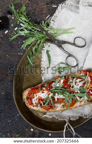 italian bruschetta with baked cherry tomatoes, parmesan cheese and rocket on toasted slice of bread on tray with vintage scissor - stock photo