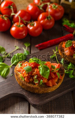 Italian bruschetta with roasted tomatoes and garlic, with herbs and basil