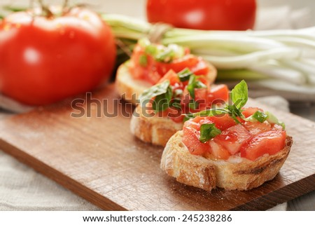 Italian bruschetta with tomatoes onion and basil, rustic food - stock photo