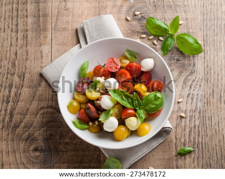 Italian Caprese salad with cherry tomatoes and mini mozzarella, selective focus - stock photo