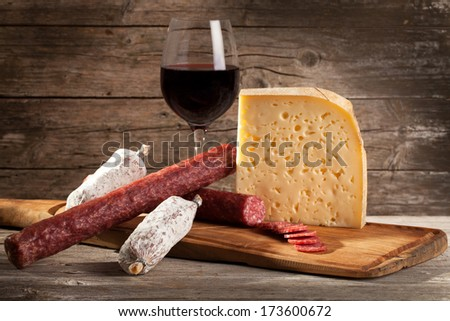 Italian cheese and salami with glass of red wine. - stock photo