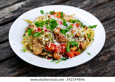 Italian Chicken Breast spaghetti with red pepper, Parmesan cheese and wild rocket  lives. on old wooden table. - stock photo