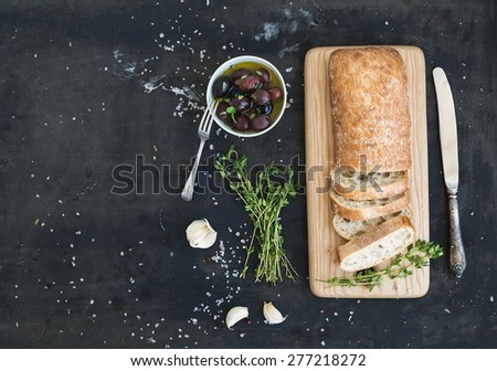 Italian ciabatta bread cut in slices on wooden chopping board with herbs, garlic and olives over dark grunge backdrop, copy space, top view - stock photo