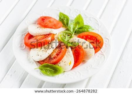 Italian classic salad caprese with mozzarella, tomato, basil and olive oil on a white background - stock photo