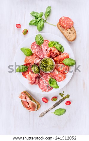 Italian cold meat plate with bread, basil pesto and tomatoes, top view - stock photo