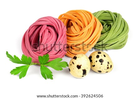 Italian colored fresh rolled fettuccine pasta with quail eggs and parsley isolated on white background. - stock photo