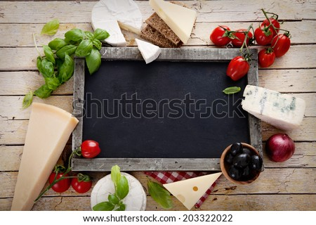 Italian cooking. Fresh ingredients with pasta for italian cuisine. Cheese variety on chalk board - stock photo