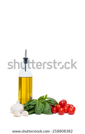 Italian cooking ingredients including a bottle of olive oil, basil leaves,garlic and cherry tomatoes isolated on white - stock photo