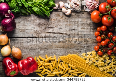 Italian cooking ingredients on a old rustic wooden table  - stock photo