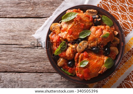 Italian cuisine: Cacciatori chicken with mushrooms on a plate. Horizontal top view