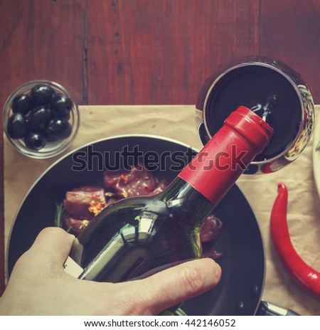 Italian Cuisine. Closeup of a man pouring red wine into a glass, a number of traditional snacks, olives, hot chili peppers, raw meat with spices cooked in a frying pan. View from above. - stock photo