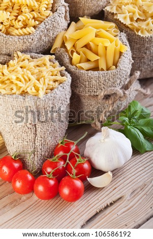 Italian cuisine concept with pasta variety in burlap bags and seasoning ingredients - stock photo