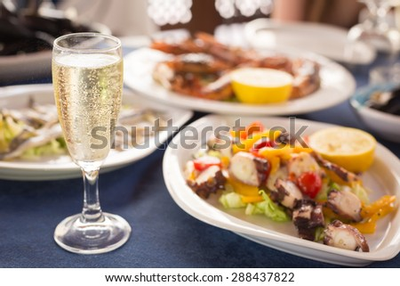 Italian cuisine. Glass of prosecco and variety of seafood. Shallow DOF, horizontal - stock photo
