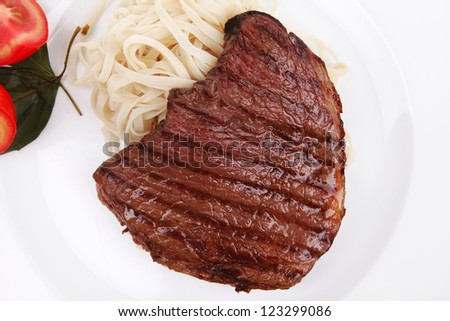 italian cuisine : grilled beef steak with pasta and tomatoes on basil leaf on plate isolated over white background