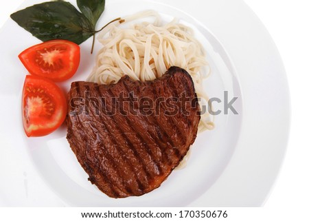 italian cuisine : grilled beef steak with pasta and tomatoes on basil leaf on plate isolated over white background - stock photo
