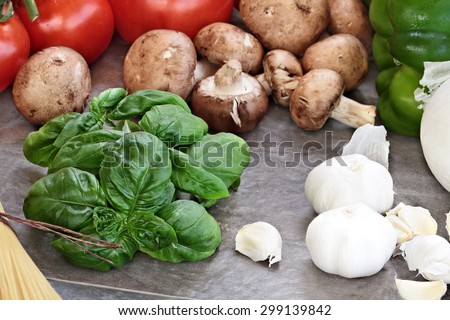 Italian cuisine ingredients of fresh basil leaves, garlic, mushrooms, onions, peppers and fresh tomatoes, Selective focus on basil with extreme shallow depth of field. - stock photo