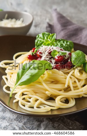 Italian cuisine. Spaghetti with parmesan cheese on a brown plate. Serving maroon cloth and a knife, fork.  gray background.
