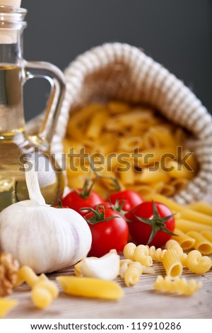 Italian cuisine typical ingredients - pasta, garlic and tomato - stock photo