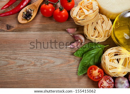 Italian cuisine. Vegetables, oil, spices and pasta on the table - stock photo