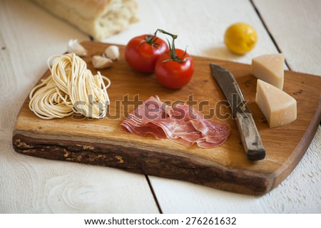 Italian delectables on a unique handmade cutting board - stock photo