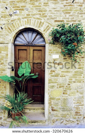 Italian Door Decorated with Fresh Flowers, Vintage Style Toned Picture - stock photo
