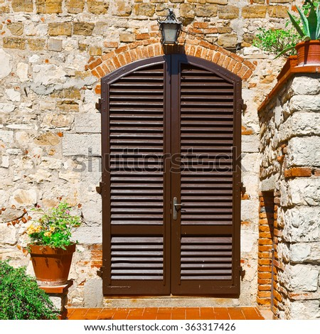 Italian Door with Closed Wooden Shutters, Decorated With Fresh Flowers - stock photo