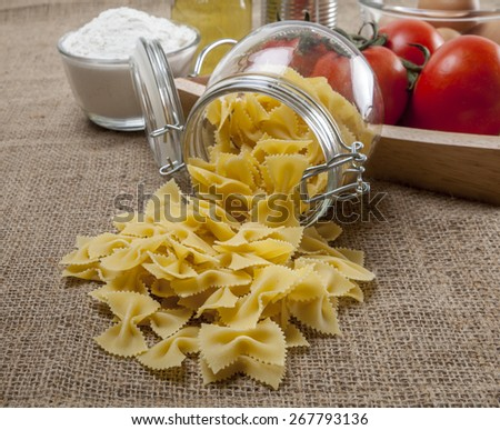 Italian farfalle pasta  ingredients sackcloth texture background - stock photo
