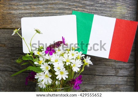 Italian flag and note for text, bouquet of wild flowers in a vase. concept for information holidays, dates and events in Italy. Information table - stock photo