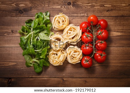 Italian flag of greens, pasta and tomatoes - stock photo
