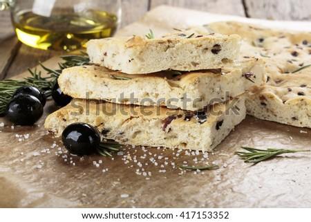 Italian focaccia bread with olives and rosemary. - stock photo