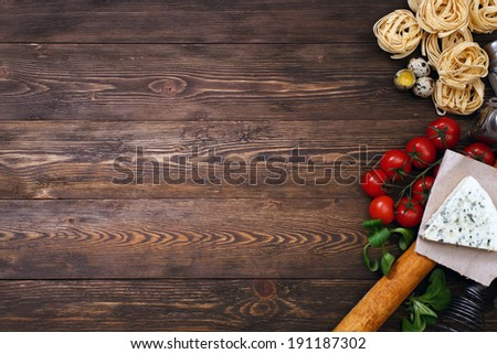 Italian food background on rustic wood boards with copyspace, with tagliatelli pasta, tomatoes, basil, cheese, grossini and condiments - stock photo
