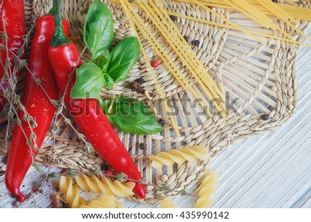 Italian food background, with tomatoes, basil, pasta, olive oil, peppercorns, chili pepper and thyme. Food concept. - stock photo