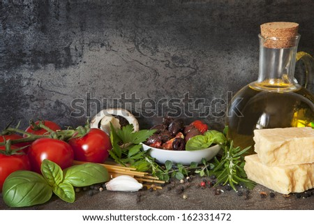 Italian food background, with vine tomatoes, basil, spaghetti, mushrooms, olives, parmesan, olive oil, garlic, peppercorns, rosemary, parsley and thyme.   - stock photo