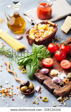 Italian food background, with vine tomatoes, basil, spaghetti, olives, parmesan, olive oil, garlic, peppercorns, rosemary,tomato sauce, parsley and thyme. Slate background. - stock photo