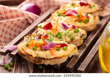 Italian food.  Bruschetta with sauce, peas, carrot, leaves of cabbage  and pepper. - stock photo