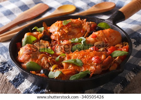 Italian food: chicken with tomato and vegetables close-up in a frying pan. horizontal