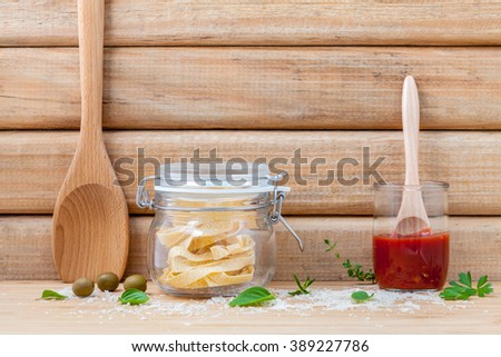 Italian food concept dried pasta with vegetables and spices herbs parsley , basil  and rosemary set up with white cheese on wooden background. - stock photo