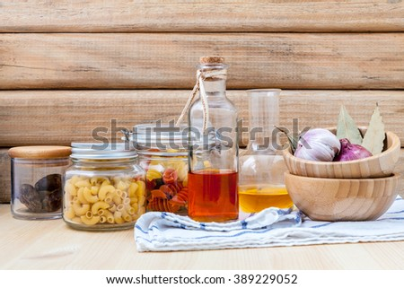 Italian food concept dried pasta with vegetables ,olive oil and spices herbs parsley , basil  and rosemary set up with white cheese on wooden background. - stock photo