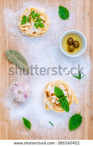 Italian food concept pasta with vegetables olive oil and spices herbs parsley , basil ,bay leaves and rosemary set up with white powder on wooden background. - stock photo