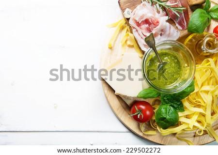 Italian food concept, pesto sauce, prosciutto ham, olive oil pasta and parmesan cheese - stock photo