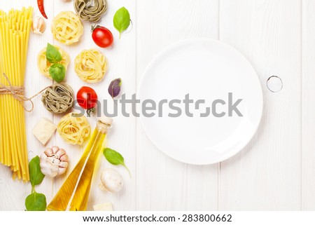 Italian food cooking ingredients and empty plate. Pasta, tomatoes, basil. Top view with copy space - stock photo
