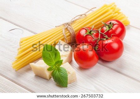 Italian food cooking ingredients. Pasta, tomatoes, basil on wooden table