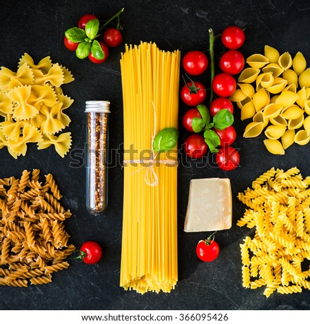 Italian food cooking pasta ingredients. Cherry-tomatoes, spaghetti, Conchiglie, fusilli, basil,  Wholewheat Fusill, Farfalle, parmesan and spices on dark grunge background, top view - stock photo